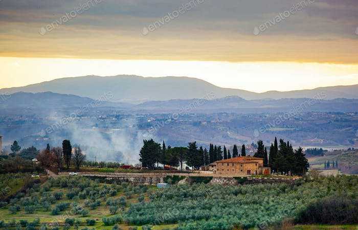 Tuscan landscape with cypress, trees and ancient buildings.