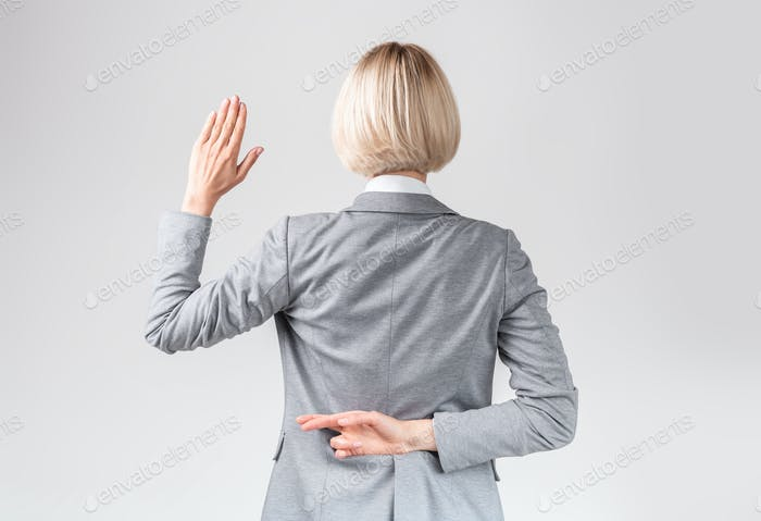 Female politician swearing oath with fingers crossed behind back on light grey studio background