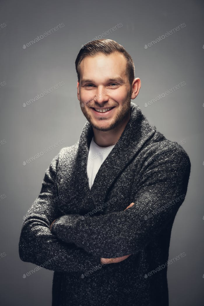 Cheerful man with crossed arms. Studio shot.