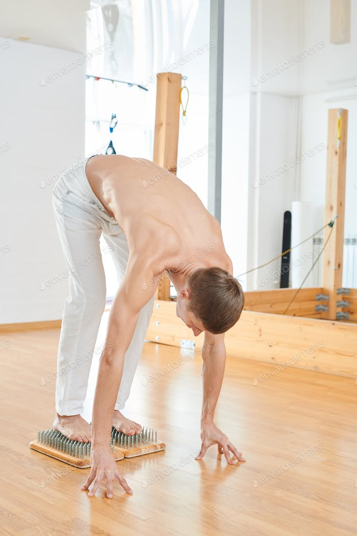Strong man easing off pain during yoga practice on nails
