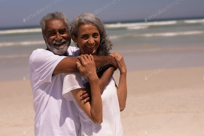 Front view of senior man embracing senior woman on beach in the sunshine