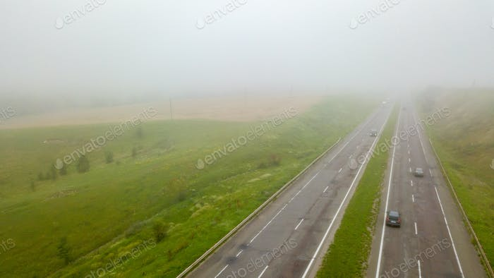 Aerial view panoramic view of the foggy road with cars around the field. Photo from the drone