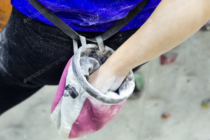 Climber woman coating her hands in powder chalk magnesium.