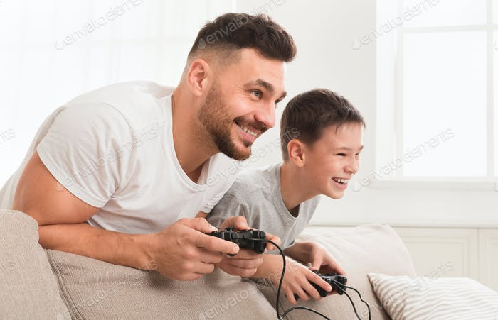 Happy boy enjoying video game with his daddy at home