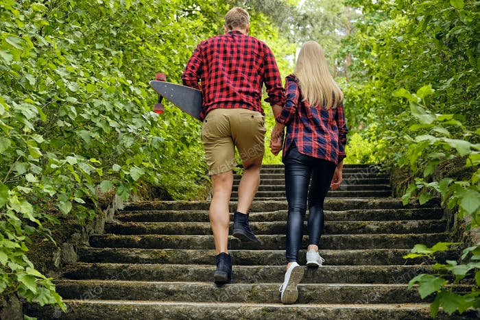 Skateboarders couple to go upstairs in nature parks.