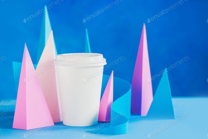 Modern coffee header. Blank paper cup on an abstract background with modern paper sculpture. Paper