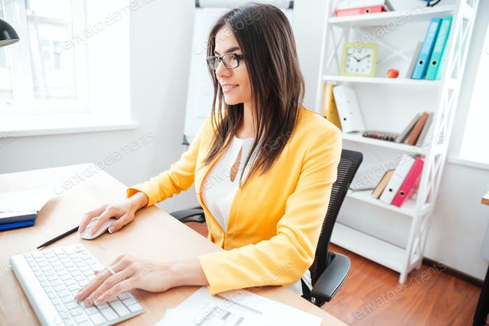 Businesswoman using keyboard and computer mouse in office