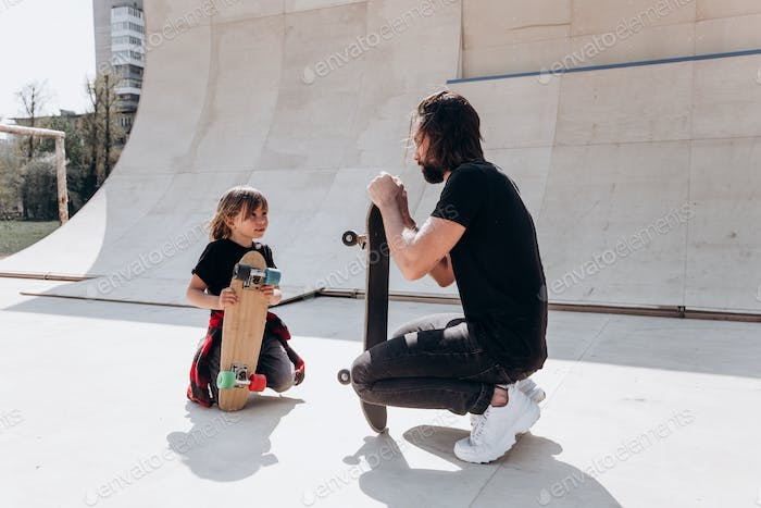 Father and his son dressed in the casual clothes are siting next to the skateboards in a skate park