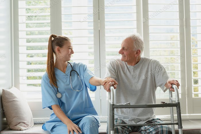 Front view of Caucasian female doctor consoling active senior man on window seat at home