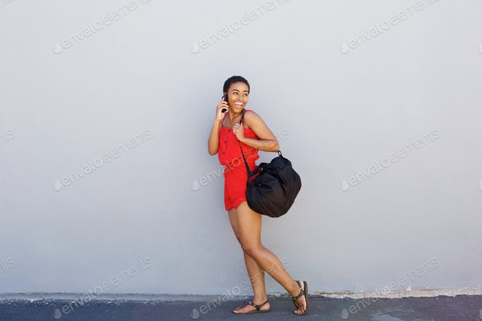 young smiling woman walking and talking on cellphone