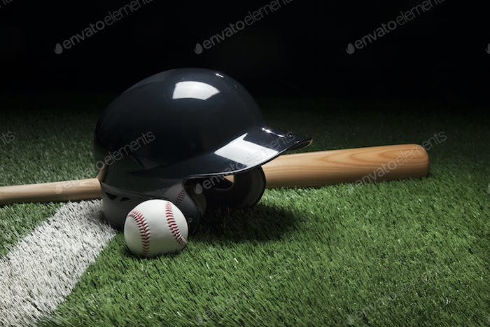 Baseball Helmet Ball and Bat on Green Field with Dark Background
