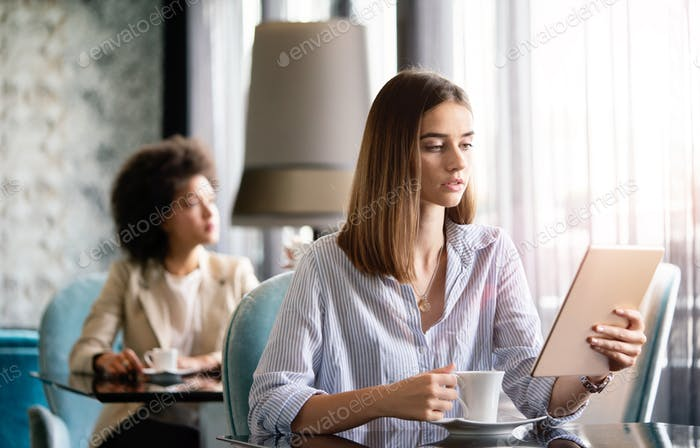 Attractive businesswoman using a digital tablet while sitting in cafe