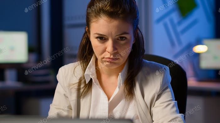 Close up of exhausted manager working overtime to respect deadline