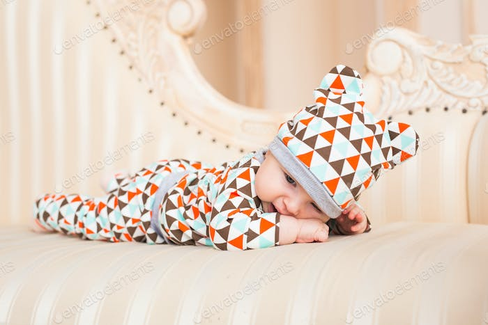 Baby, childhood and newborn concept - little child lying on the couch in the coloured cap.