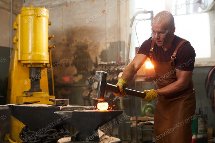 Strong man working in smithy