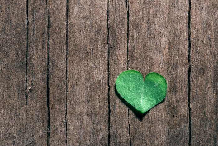 Heart-shaped part of shamrock leaf on shabby wooden background.
