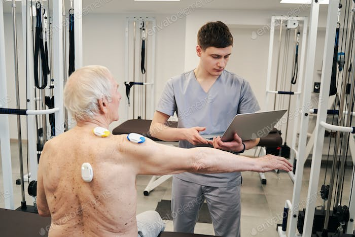 Physical therapist with laptop conducting back muscles diagnostics for retiree