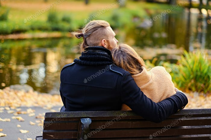 Rear view of couple sits on a bench.