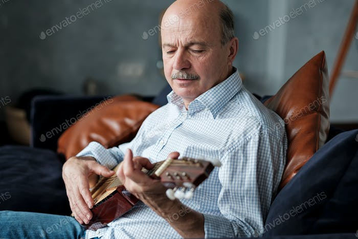 Senior hispanic man at home learning to play guitar.