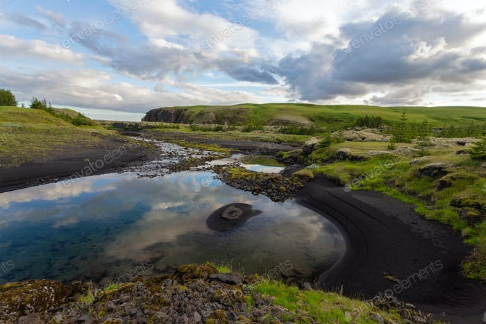 Summer nature scenery with black sand on a riverbank and clouds in the sky
