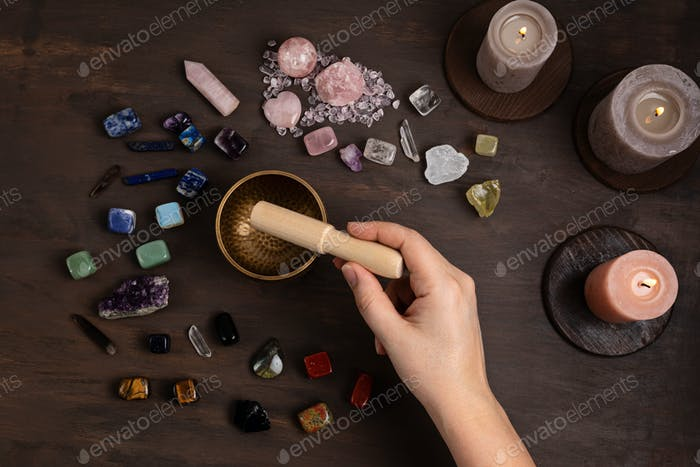 Woman cleansing healing chakra crystals with tibetan singing bowl. Rituals with gemstones for