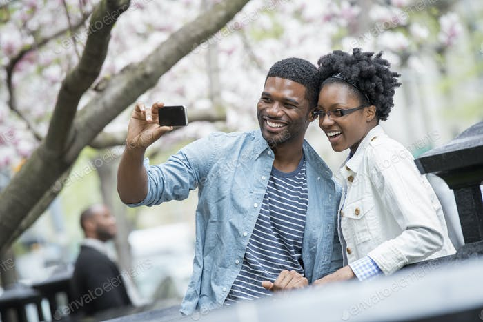 Im  Frühling im Freien in der Stadt. Ein Paar, das ein Selfie mit einem Handheld-Handy macht.