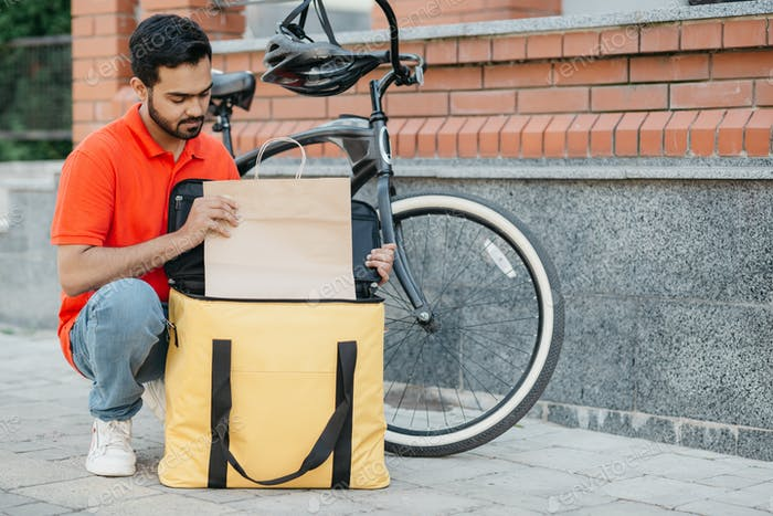 Kurier und Paket für den Kunden. Besetzt Kerl Kurier in Uniform mit Fahrrad bringt Waren in Tasche