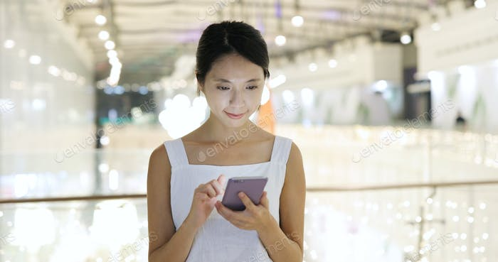 Woman use of mobile phone and walking inside shopping mall