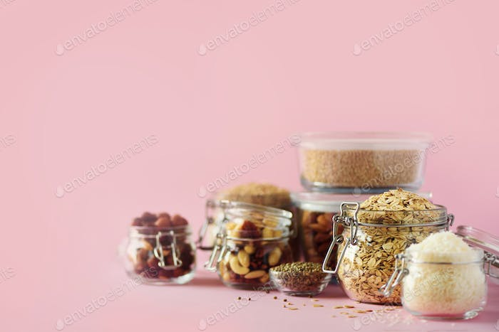 Grains, cereals, nut, dry fruits in glass jars over pink background with copy space. Clean eating