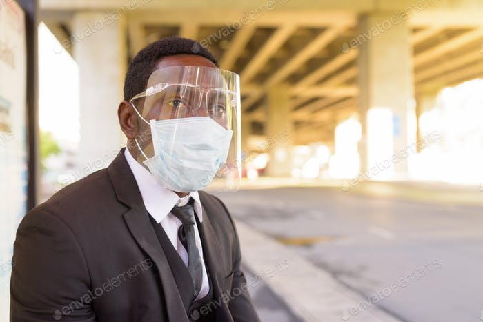 African businessman with mask and face shield waiting at the bus stop in the city outdoors