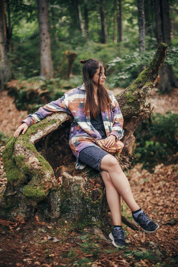 chica viajero con estilo sentado en el viejo tocón con musgo en el bosque soleado y las montañas