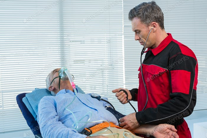 Paramedic checking blood pressure of patient