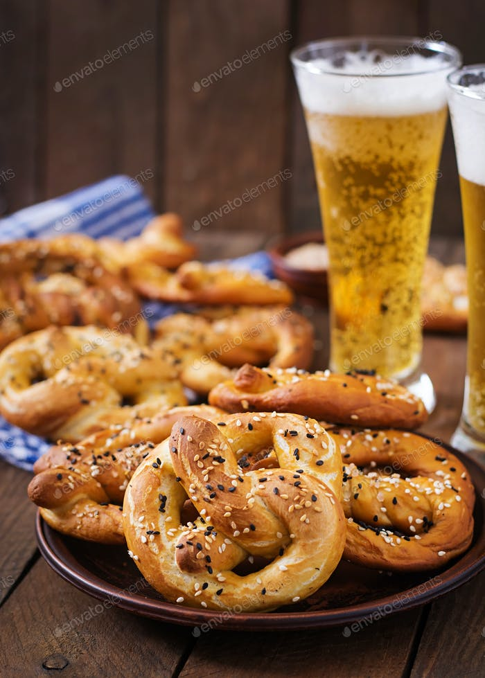 Oktoberfest salted soft pretzels in a bowl and beer from Germany on wooden background.