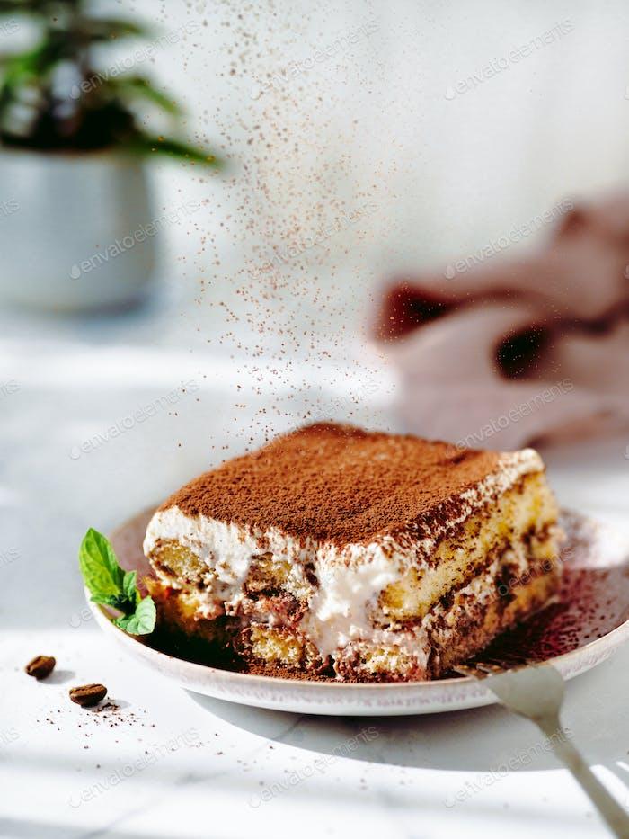 Tiramisu sprinkled with cocoa powder, vertical