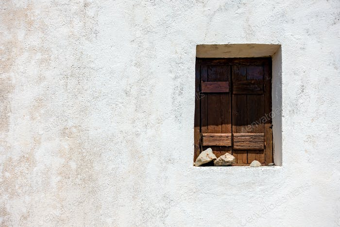 Wooden window on old white wall
