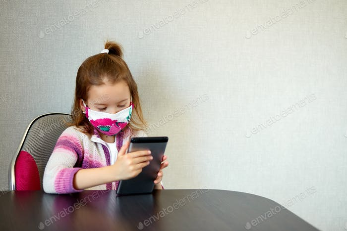 Young child girl at home, wearing a protection mask and gaming on a tablet, Coronavirus quarantine.