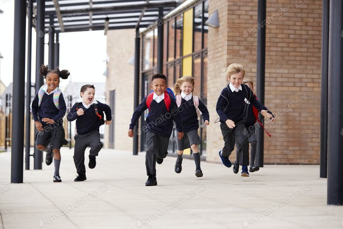 Primary school kids, wearing school uniforms and backpacks, running on a walkway