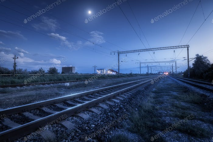 Railroad and blue sky with moon and clouds at night