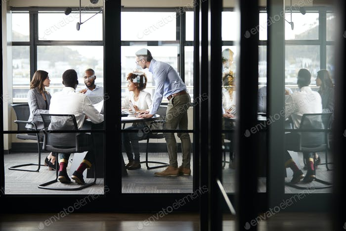 Middle aged white businessman stands addressing colleagues at meeting, seen through glass wall