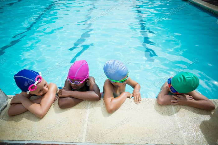 Little swimmers talking while leaning at poolside