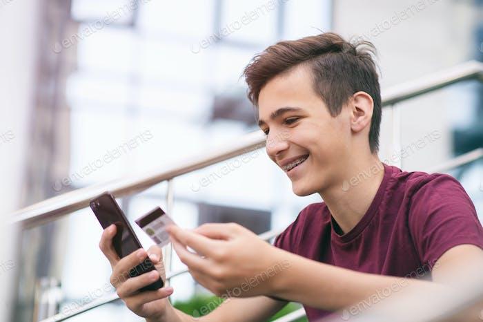 Adolescente con tarjeta de crédito y teléfono móvil