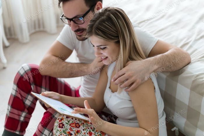 Young attractive couple using digital tablet in bedroom