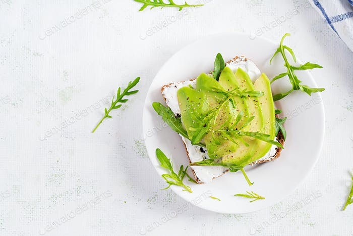 Sandwich of cream cheese bread and slices of avocado on a plate on a light background.