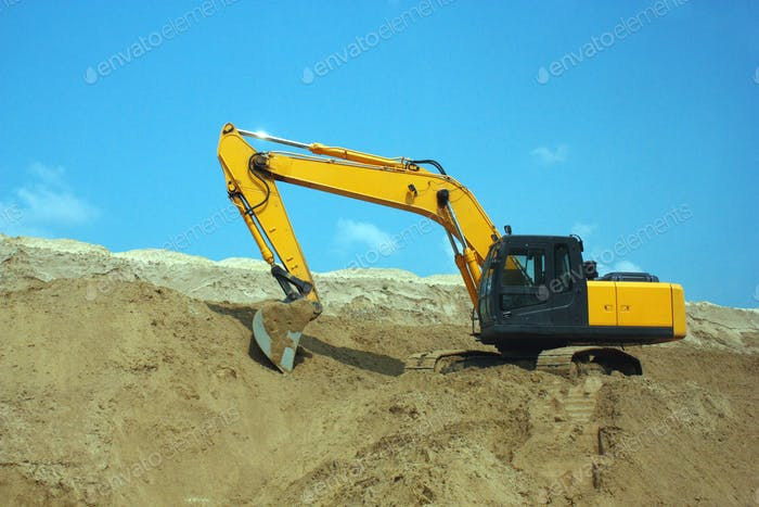 Yellow excavator, excavation work at a construction site.