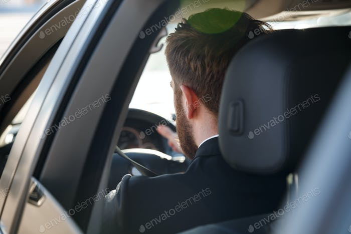 View from back of Business man driving car