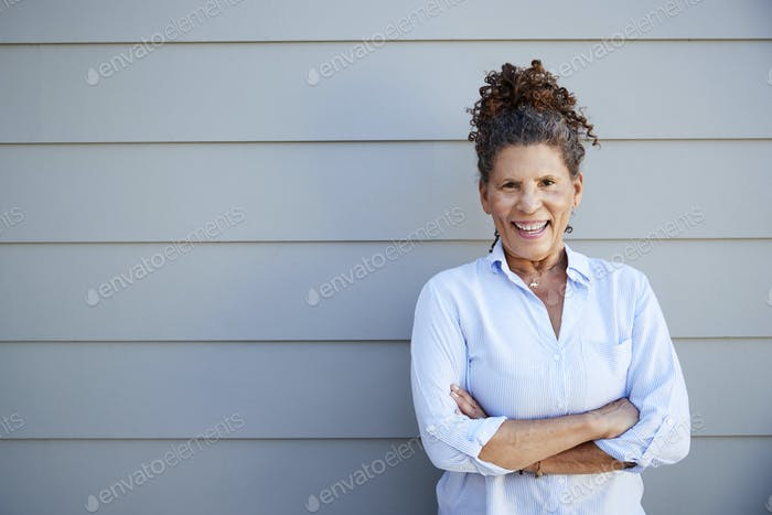Portrait Of Senior Woman Standing Outside Grey Clapboard House