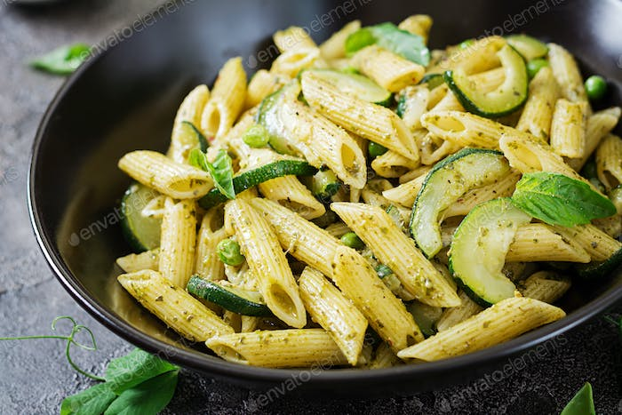 Penne pasta with  pesto sauce, zucchini, green peas and basil. Italian food.