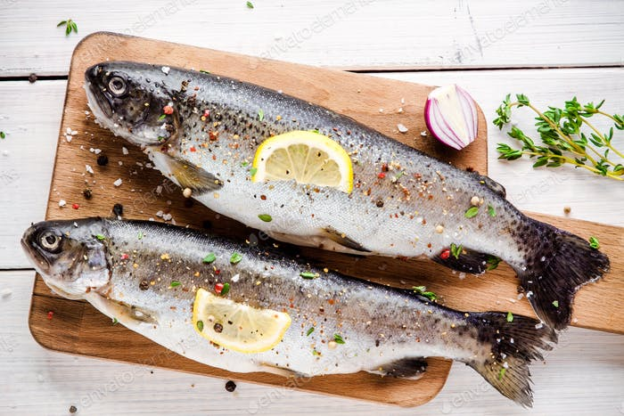 two raw trouts on cutting board with thyme, lemon and red onion