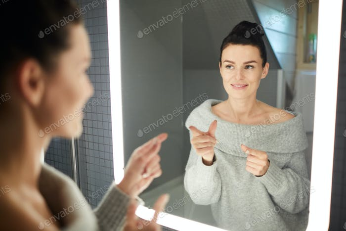 Confident woman pointing finger guns into mirror