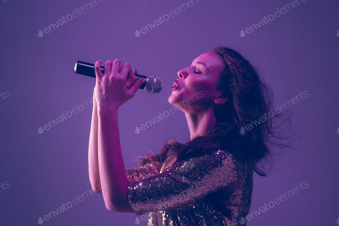Caucasian female singer portrait isolated on purple studio background in neon light